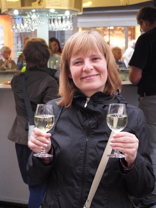 holding two glasses of wine at a wine stand in Trier